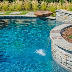 Stone retaining wall with custom-built waterfalls & landscaping