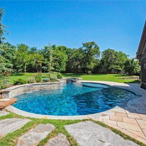Stone walkway to inground custom-built pool