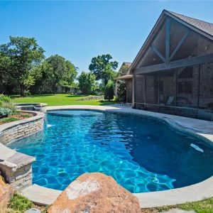 Custom pool with water feature and stone patio