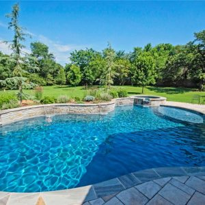Pool with stone edging, retaining wall, and landscaping