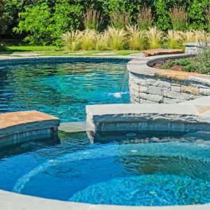 Custom-built stone hot tub with pool and waterfalls