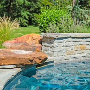 Stone retaining wall with custom-built waterfalls and landscaping