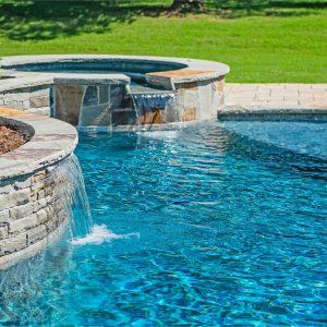 Stone retaining wall with custom-built waterfalls