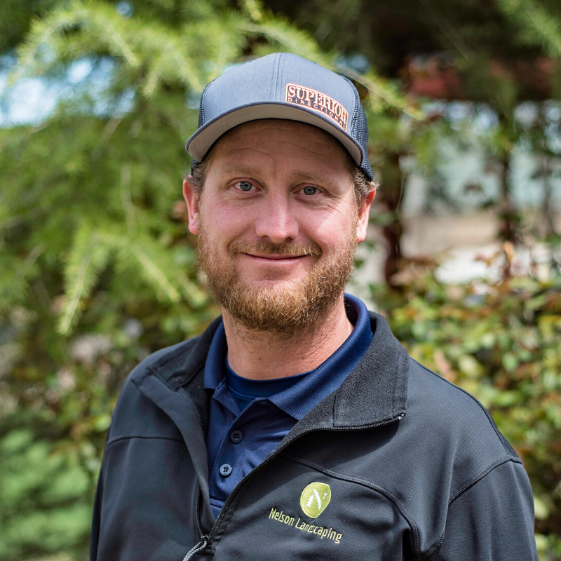 Justin from Nelson Landscaping smiling in a backyard setting.