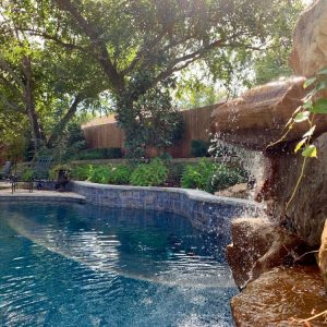 Backyard pool with waterfall and pavilion designed for Jeff Roberts from KMGL Magic 104.1 radio