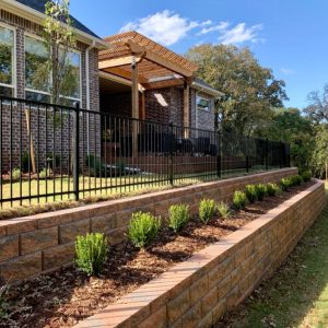 Looking down stone retaining wall and landscaping by Nelson Landscaping