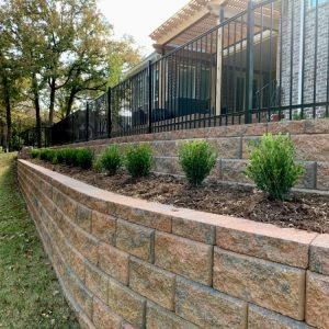 retaining wall project with plants and fencing