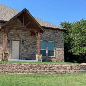 Wood arch home entry with retaining wall in front yard