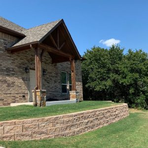 Wooden arch leading to house entry with retaining wall