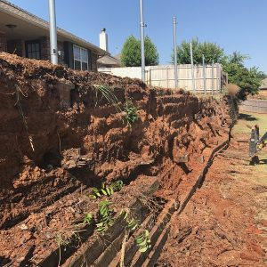 retaining wall is a structure that stabilizes and holds Red Oklahoma soil in place