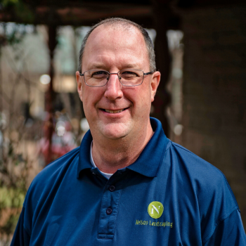 Scott is wearing his bright blue Nelson Landscaping polo shirt.