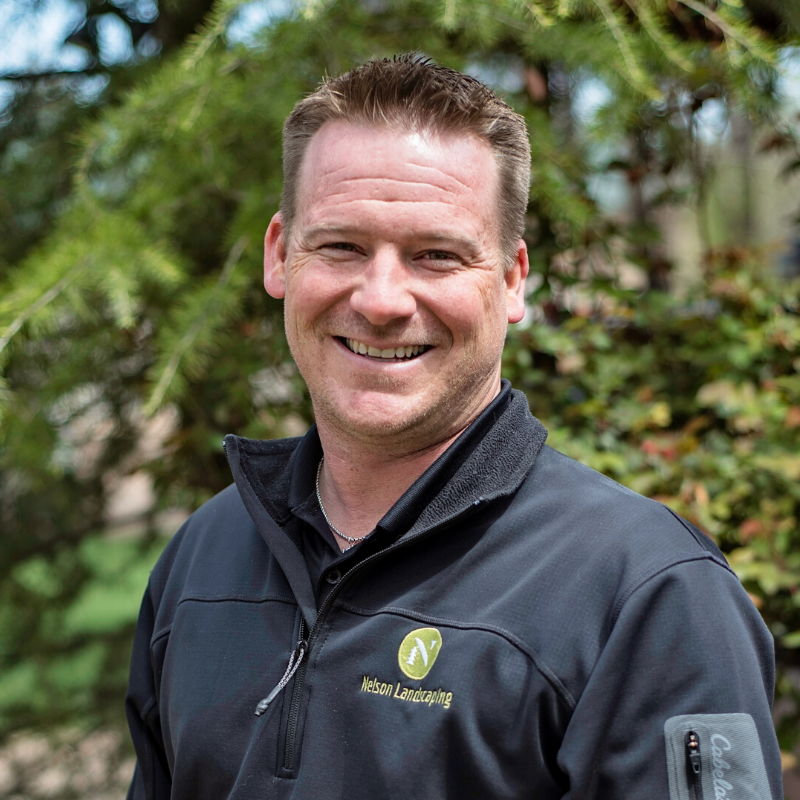 Travis from Nelson Landscaping smiling in an outdoor setting.